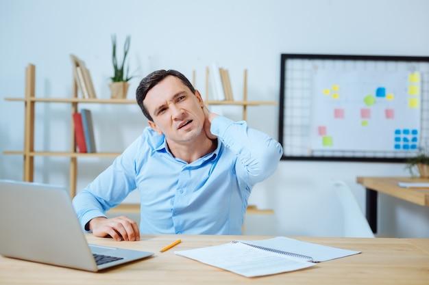 Chcesz mieć masaż. poważny mężczyzna siedzi w miejscu pracy i patrząc na bok podczas przerwy
