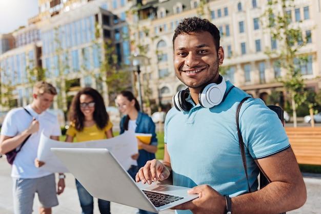 Chcesz się uczyć. przystojny brunetka, trzymając uśmiech na twarzy i trzymając słuchawki na szyi, patrząc na kamery