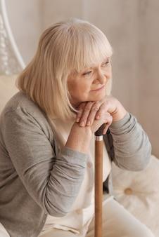 Chciałabym być znowu młoda. miła, rozmarzona starsza kobieta trzymająca laskę i rozmyślająca o swojej przeszłości podczas odpoczynku w domu