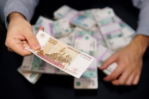 Chciwe męskie ręce sięgają po zwitek pieniędzy. milion rubli rosyjskich na czarnym stole. pojęcie bogactwa, sukcesu, chciwości i korupcji, żądzy pieniędzy. kapitał, kapitalizm