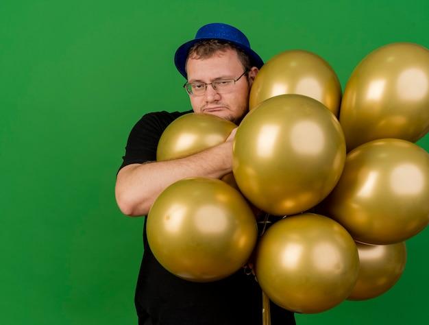 Chciwy dorosły słowiański mężczyzna w okularach optycznych w niebieskiej imprezowej czapce trzyma balony z helem