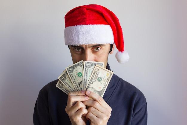 Chciwy mężczyzna w kapeluszu świętego mikołaja trzymający banknoty dolarowe zakrywające twarz na białym tle