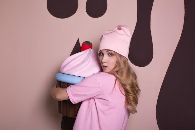 Chciwy młody blond model w różowej koszulce i czapce, pozujący z dużą słodką dekoracją babeczki