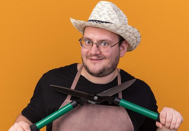 Chciwy młody mężczyzna ogrodnik w kapeluszu ogrodniczym i rękawiczkach, trzymający maszynki do strzyżenia wokół twarzy odizolowanej na pomarańczowej ścianie
