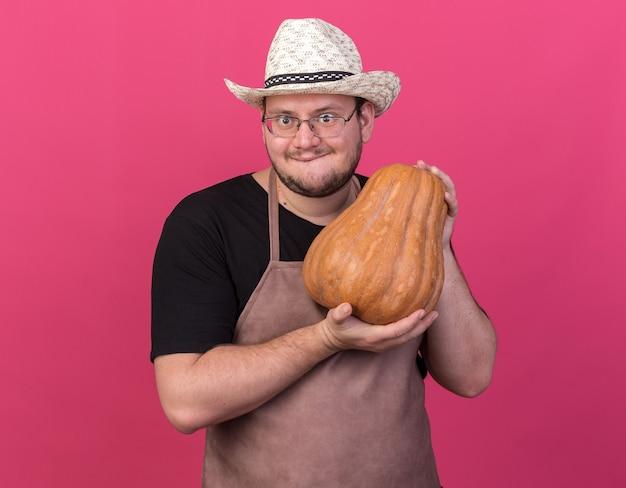 Chciwy młody mężczyzna ogrodnik w kapeluszu ogrodniczym trzymający dynię odizolowaną na różowej ścianie