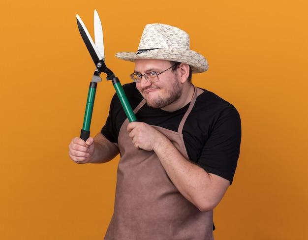 Chciwy młody ogrodnik mężczyzna w kapeluszu ogrodniczym i rękawiczkach, trzymając maszynkę do strzyżenia na białym tle na pomarańczowej ścianie