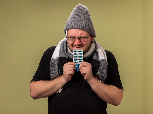 Chciwy, patrzący na kamerę, chory mężczyzna w średnim wieku, ubrany w zimową czapkę i szalik trzymający pigułki