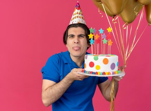 Chciwy przystojny kaukaski mężczyzna w czapce urodzinowej z wystającym językiem trzyma balony z helem i tort urodzinowy