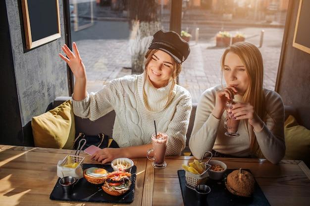 Cheeerful młoda kobieta w czapce siedzieć przy stole z koleżanką. macha ręką i uśmiecha się. drugi model wypić koktajl. mają jedzenie przy stole.