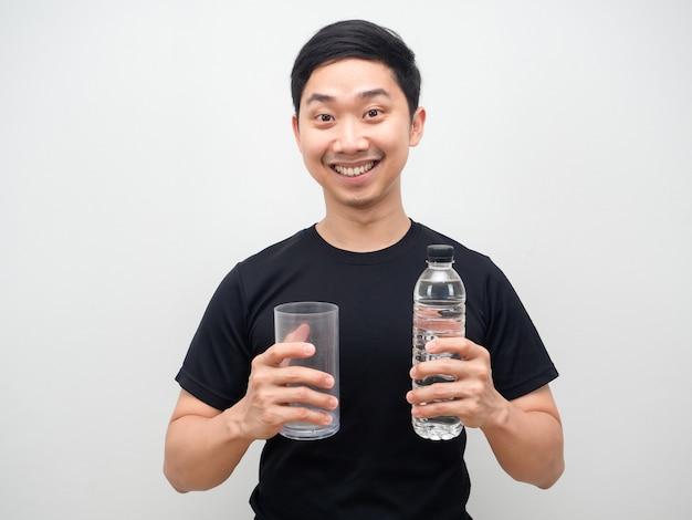 Cheefull mężczyzna azjatycki trzyma butelkę wody i szklankę w ręku na białym tle