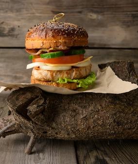 Cheeseberger z bułką, mięsem i warzywami na drewnianej powierzchni, fast food