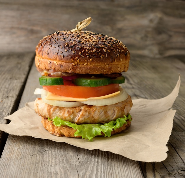 Cheeseberger z bułką, mięsem i warzywami na drewnianym stole, fast food