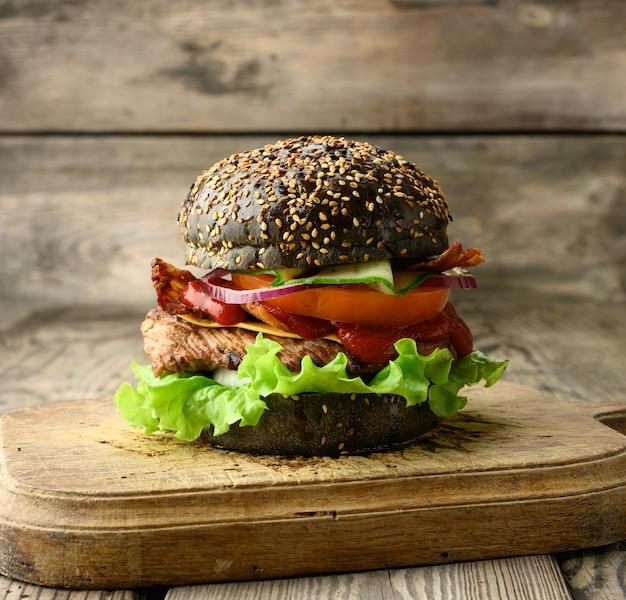 Cheeseberger z czarną bułką, mięsem i warzywami na drewnianej powierzchni, fast food