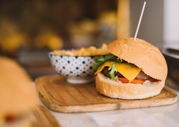Cheeseburger dla smakoszy podawany z domowym chlebem i frytkami