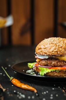 Cheeseburger jusy na ciemnym drewnianym stole