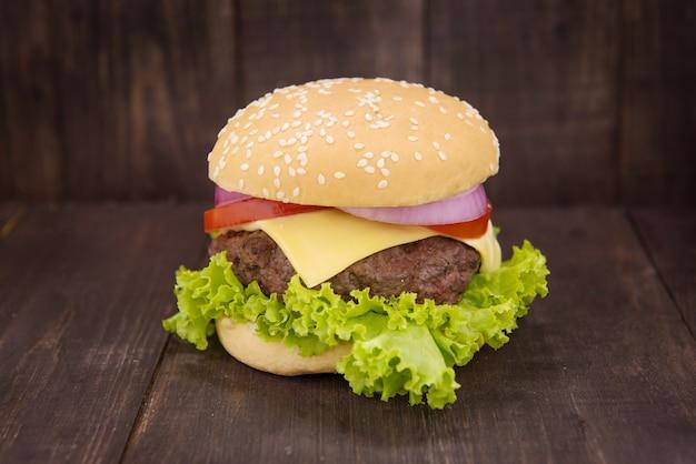 Cheeseburger na babeczkach z tłustoszowatą wołowiną na drewnianym tle