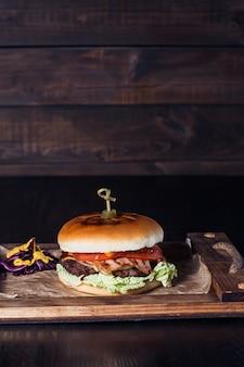Cheeseburger na drewnianej tacy w restauracji na ciemnym tle.