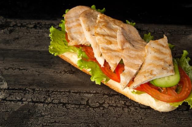 Cheeseburger na starej drewnianej powierzchni ciemnego koloru hamburger z mięsem z kurczaka na starym drewnianym