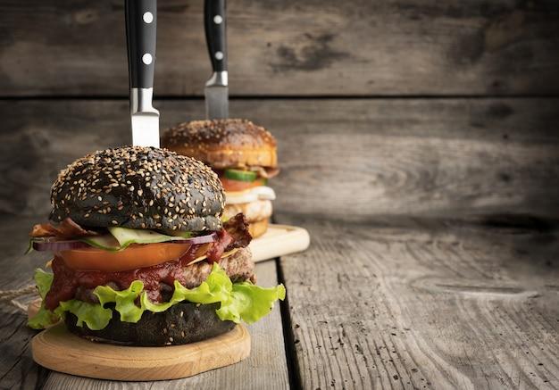 Cheeseburger z czarną bułką, mięsem i warzywami na drewnianej powierzchni, fast food i nóż, miejsce na kopię