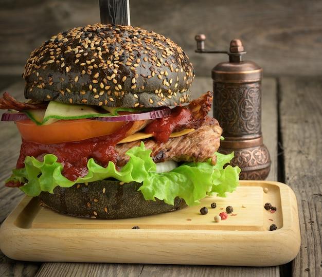 Cheeseburger z czarną bułką, mięsem i warzywami na drewnianej powierzchni, fast food