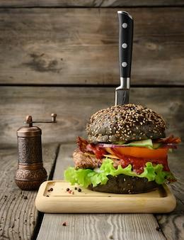 Cheeseburger z czarną bułką, mięsem i warzywami na drewnianym stole, fast food