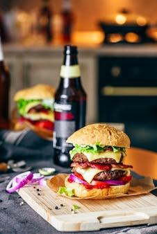 Cheeseburger z dwoma pasztecikami wołowymi, serem cheddar, boczkiem, sałatą lodową, pomidorami w plasterkach i czerwoną cebulą. butelka piwa i niektóre składniki na stole.