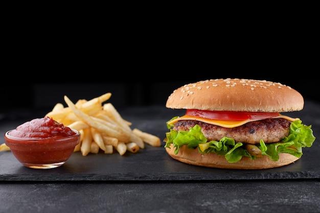 Cheeseburger z mięsem, ziemniakami i sosem, na czarnym kamieniu