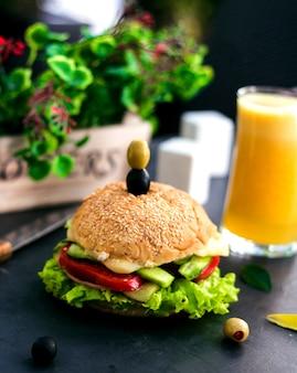 Cheeseburger z oliwkami na wierzchu i sokiem