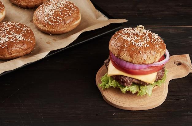 Cheeseburger z pomidorami, kotletem z grilla i bułką sezamową na starej drewnianej desce do krojenia, brązowa przestrzeń. fast food, widok z góry