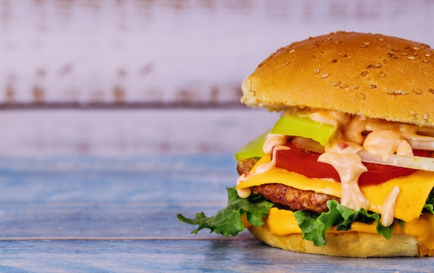 Cheeseburger z roztopionym serem na białym stole.