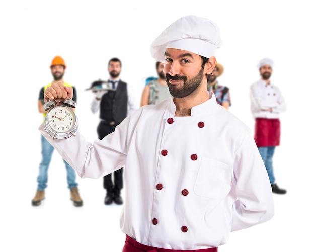 Chef trzyma zegar na białym tle