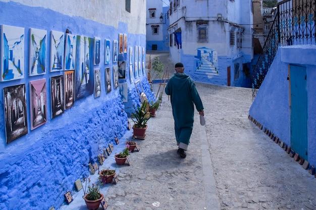 Chefchaouen, maroko. lokalny mężczyzna w tradycyjnych strojach idzie na ulicę chefchaouen