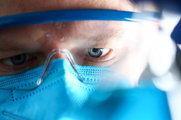 Chemia mężczyzna jest ubranym ochronną maskę trzyma w ręki próbnej próbce