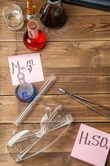 Chemiczne kolby, pincety, klawiatura, zeszyty na drewnianym stole z lato.