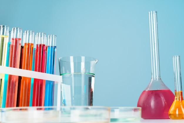 Chemiczne szkło laboratoryjne z różnymi kolorowymi płynami na stole