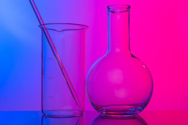 Chemiczne wyroby szklane z bliska na neonowo różowo-fioletowym tle