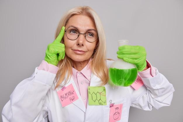 Chemik bada substancja chemiczna trzyma palec na skroni ma sprytny wygląd przeprowadza eksperyment w laboratorium nosi okrągłe okulary biały fartuch medyczny badania biochemia
