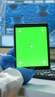 Chemik człowiek ubrany w kombinezon ochronny, trzymając tablet z zieloną makieta w nowocześnie wyposażonym laboratorium. zespół mikrobiologów prowadzących badania nad szczepionkami piszący na urządzeniu z kluczem chrominancji, izolowany wyświetlacz.