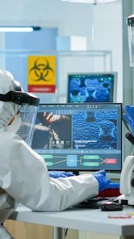 Chemik kobieta w garniturze ppe pisania na komputerze sprawdzanie rozwoju wirusa w wyposażonym laboratorium. zespół lekarzy pracujących z różnymi bakteriami, próbkami tkanek i krwi, badania farmaceutyczne nad antybiotykami