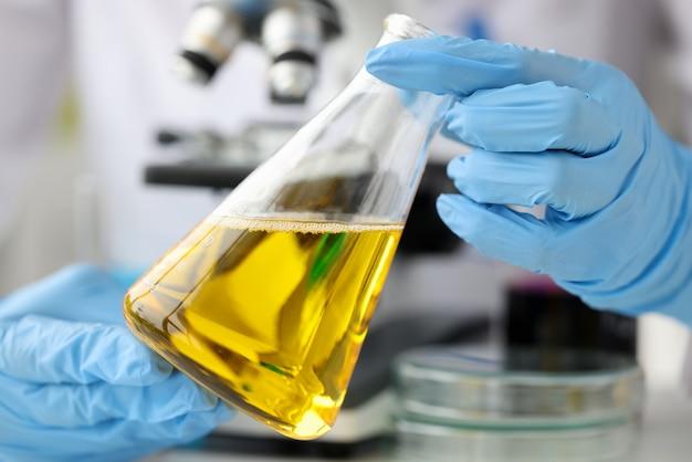 Chemik naukowiec trzymając szklaną kolbę z żółtym płynem przed jakością zbliżenia mikroskopu