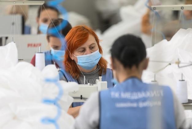 Chernigiv, ukraina - 06.10.2020: szycie kombinezonów ochronnych dla lekarzy i lekarzy podczas pandemii covid-19 w szwalni tk-style w czernihowie na ukrainie