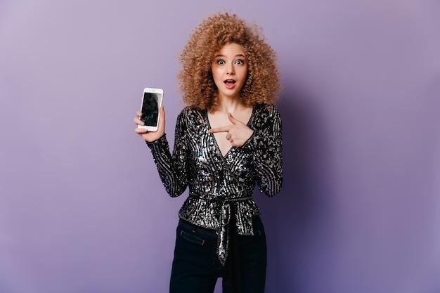 Chętna kobieta o niebieskich oczach i kręconych włosach ubrana w błyszczącą dyskotekową bluzkę wskazuje na smartfona.