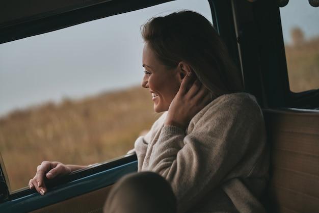 Chętnie podróżuję. atrakcyjna młoda kobieta wygląda przez okno furgonetki i uśmiecha się siedząc na przednim siedzeniu pasażera