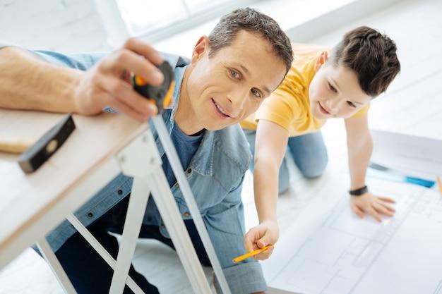 Chętny do pomocy. przyjemny chłopiec w wieku przedszkolnym pomaga ojcu zmierzyć nogę stołu, sprawdzając taśmę mierniczą, której używa ojciec, przed przystąpieniem do rysowania planu