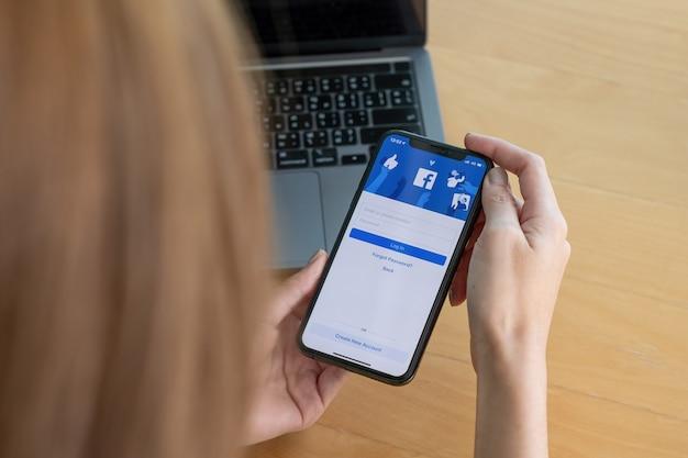 Chiang mai, tajlandia - 03 października 2018: logo aplikacji społecznościowej facebook na logowanie, rejestracja strony rejestracji na ekranie aplikacji mobilnej na iphone x w dłoni osoby pracującej w biznesie e-commerce.