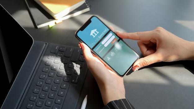 Chiang mai tajlandia, styczeń, - 31, 2020: kobieta trzyma iphone z bankowości online ekranem. bankowość internetowa pomaga zarządzać pieniędzmi