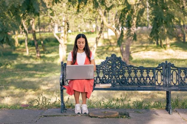 Chica trabajando pl el parque con su computadora portatil sentada pl una banca con arboles