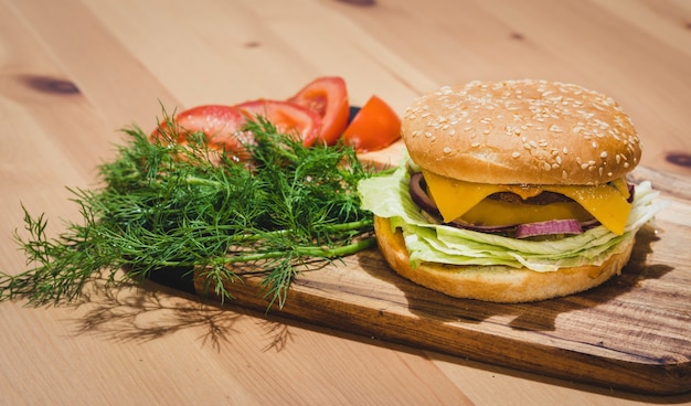 Chicken burger with fresh tomatoes and dills, set on wooden board with copy space on top