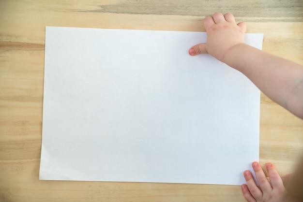 Children ręka trzyma pustego białego papieru prześcieradło na drewnianym tle.