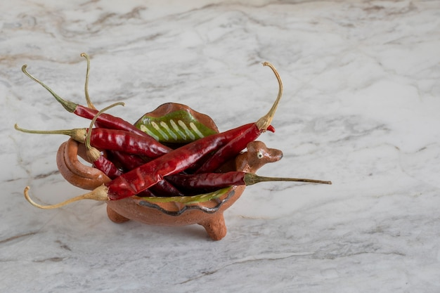Chiles de arbol lub suszone czerwone papryczki chili w glinianym garnku na szarej marmurowej kostce